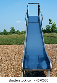 Metal playground slide on the edge of field