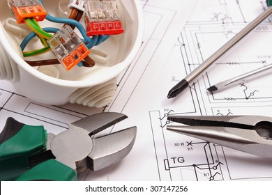 Metal pliers, screwdriver and cable connections in electrical box lying on electrical construction drawing of house, work tool and drawing for engineer jobs, concept of building house