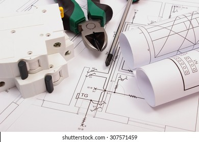 Metal pliers, screwdriver, electric fuse and rolls of diagrams on electrical construction drawing of house, work tool and drawing for projects engineer jobs, concept of building house
