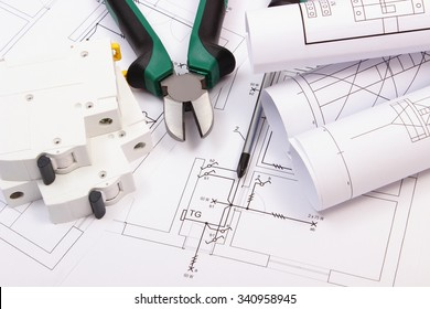 metal pliers, screwdriver, electric fuse and rolls of diagrams on electrical  construction drawing of