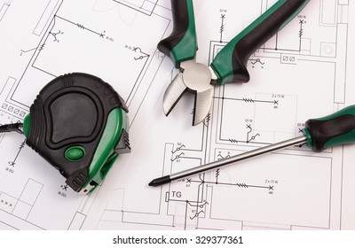 Metal pliers, screwdriver and tape measure on electrical construction drawing of house, work tools and drawing for projects engineer jobs, concept of building house