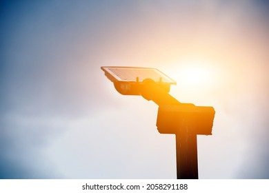 Metal pole of streetlamp which has mini solar cell panel above, sunset background. sustainable energy in daily life concept. Soft and selective focus.
