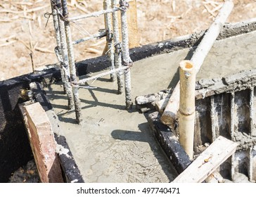 metal pole in wet concrete  of  house foundation at construction site