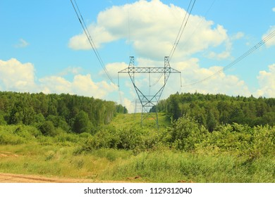 Metal poles of power lines. High-voltage direct current line. Power transmission towers. Close-up on nature.
