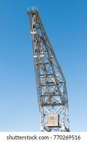 metal port crane with three hooks and blue sky