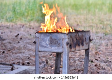 Metal portable barbecue with burning firewood and red flames. Barbecue outdoor.  Bonfire for cooking meat. Fire and coal in the grill. Brazier equipment. BBQ picnic. Flaming wood with fire and ashes
