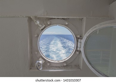 metal porthole scuttle on a fast ferry with the view of the backwash and waterway