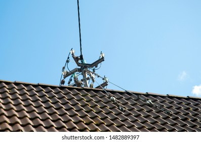 metal post on top of a roof for power distribution with cables and glass insulators