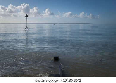 Metal post with a triangle on top near the seashore  acts as a warning sign, it marks a hazard beneath the surface.