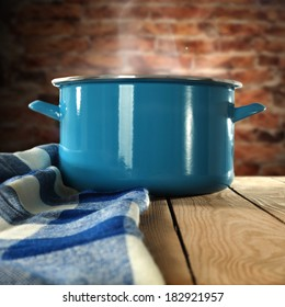 metal pot blue napkin and brown wall of bricks