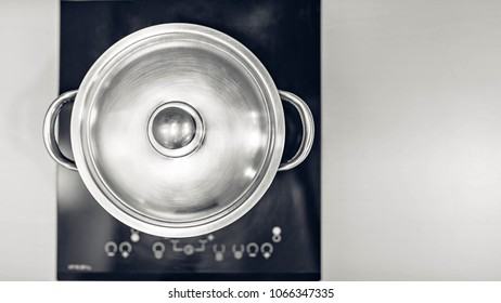 Metal pot on the cooker. Top view. Flat lay. Black and white.