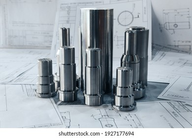 Metal products turned on a lathe lie on the drawings against the background of other drawings. Metalworking of products on CNC machines at the plant.