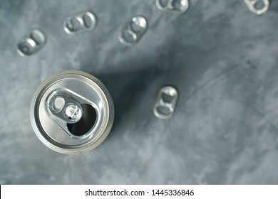 Metal pull tabs of beverage can on gray table. Many aluminum can. Recycle concept. Copy space.