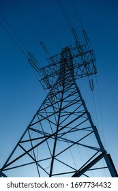 Metal pylon of a power line against a clear blue sky