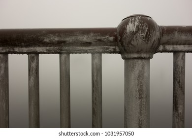 Metal railing against a foggy background. Mood of mystery and the unknown. Feeling of abandonment and decay.