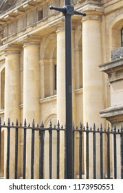 Metal railing and lamp post in front of Ionic columns, Oxford.