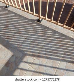 Metal railings throwing angled shadows across tiled patio.