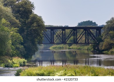 A metal railway bridge crossing a span of the Grand River, shot from an opposing bridge in St. Jacobs, Ontario.