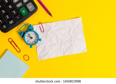 Metal retro vintage alarm clock wakeup clips crushed sheet note notepad rubber band calculator pencil lying colored background empty text important events what to do office school home
