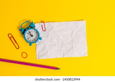 Metal retro vintage alarm clock wakeup clips crushed sheet note rubber band pencil lying colored background empty text important events what to do office school home