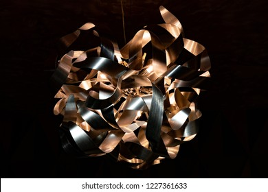 Metal ribbon chandelier closeup. Modern lampshade. Copper and silver textured background. Abstract chaotic pattern. Futuristic abstract backdrop in shades of brown. Interior decoration.