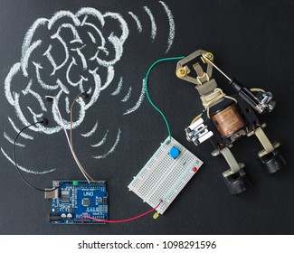The metal robot is connected to Arduino and the drawn human brain. Concept. Idea. Education. Mind. New Intelligence. AI.