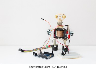 A metal robot and an electronic board that can be programmed. Robotics and electronics. Laboratory in the school. Mathematics, engineering, science, technology, computer code. STEM education for kid.