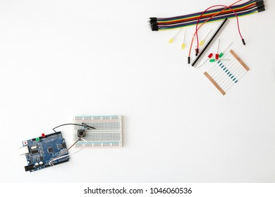 A metal robot and an electronic board that can be programmed. Robotics and electronics. Arduino in the school. Mathematics, engineering, science, technology, computer code. STEM education for kid.