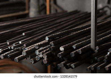 Metal rods for the building of houses lie in the row. Close up of metal armature of different thickness lying in row on rack in blacksmith workshop.