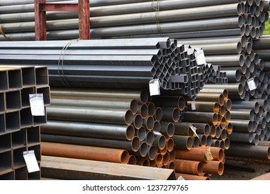Metal rolling. A round and square tube with labels for text are stacked in storage for sale and loading in stock in the open air. Close-up.