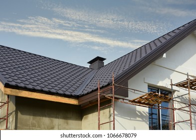 Metal roof construction with coaxial chimney pipe heating system against blue sky.