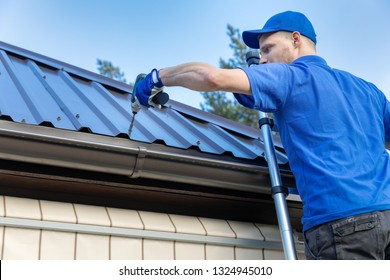 metal roofing - roofer working on the house roof