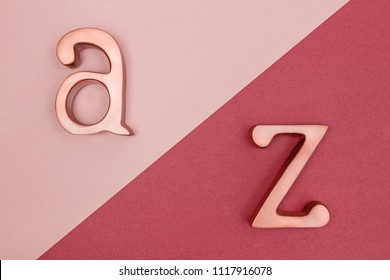 Metal rose gold letters A and Z on pink and cherry red background.