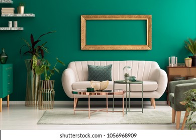 Metal, round coffee tables and a beige sofa in a green, luxurious living room interior with marble shelves and golden decorations