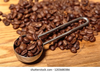 Metal Round Spoon with Coffee Beans on Brown Wooden Bench Top