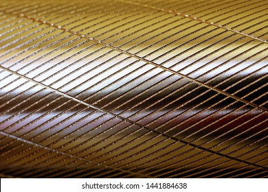 Metal round surface with longitudinal and transverse notches. Golden shade. Background and pattern. Daylight.