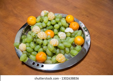 Metal round tray with grapes and tangerines. It is located on a wooden surface. Close-up.