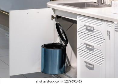 metal rubbish bin under sink hanging on kitchen cupboard door.