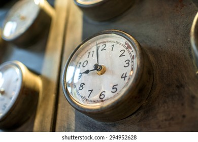 Metal rusted wall with old styled clocks and different time