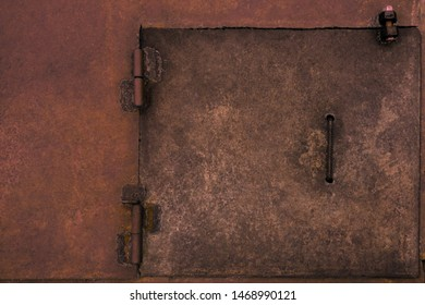 Metal rustic door hatch. Weathered vintage industrial surface with welding spots and rust. Dirty red rough pattern background