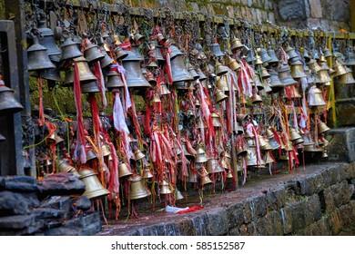Metal sacrificial bells hanging on chains in Dakshinkali hindu temple in Pharping, Nepal