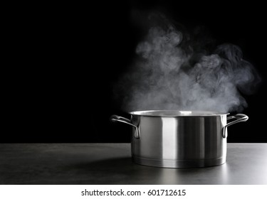 Metal saucepan with hot liquid on table against dark background
