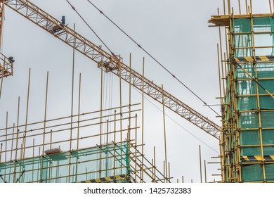 Metal scaffolding guardrails and tower cranes on the top of a building under cloudy weather
