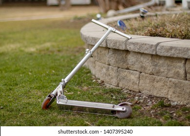 A metal scooter resting against a stone retaining wall on an abandoned farm in Collingwood, Ontario during a spring evening.