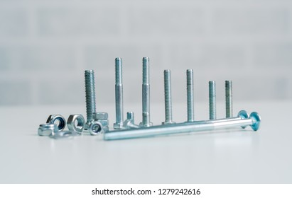 Metal screw, bolt and nuts on white background.