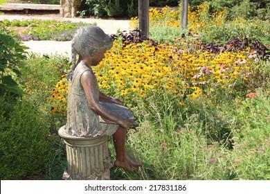 Metal sculpture of a girl reading near a flower garden
