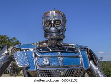 Metal sculpture of robot or knight made of details of old cars. Camp of bikers. Russia