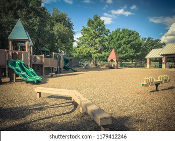 Metal seesaw balance at public wooden children playground under the lush of larger trees in Coppell, Texas, USA. Play set outdoor toys surrounded by summer leaves green and cloud blue sky