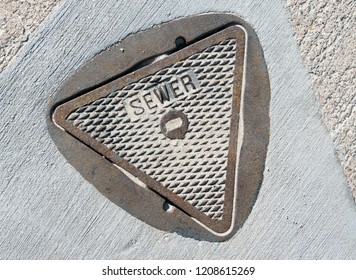 Metal sewer cover in pavement covered with sand. Triangle shape. Raised letters with the word sewer.