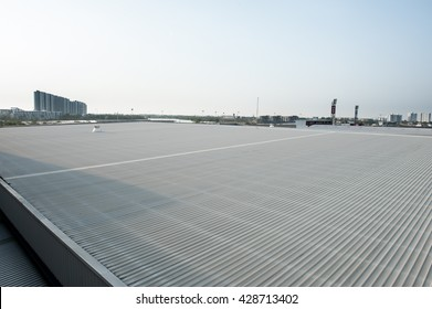 Metal sheet roof with blue sky and white clouds background.